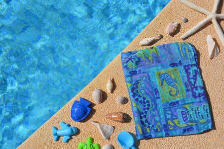 Seashells, beach wrap and beach toys at the edge  of a swimming pool. Summer flat lay, creative concept. Banco de Imagens