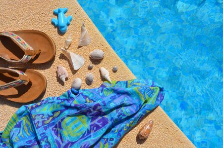 Flip flops, seashells, beach wrap and toy blue aeroplane at the edge  of a swimming pool. Summer flat lay, creative concept.