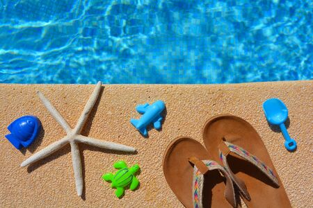 Summer holiday flat lay. Sandals, starfish and beach toys next to a swimming pool. High angle view with copy space. Banco de Imagens