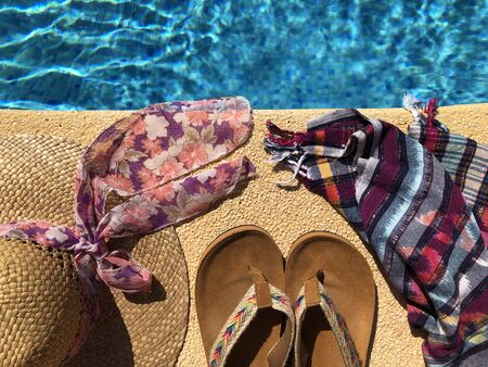 Summer flat lay, straw hat, beach wrap and sandals on the side of a blue tiled swimming pool, seen from above Banco de Imagens