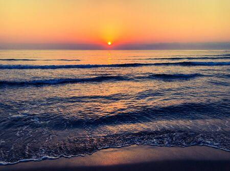 Sunrise over sea, view to horizon from sandy beach