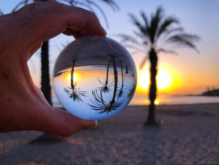 Womans hand holding a crystal ball, looking through a palm grove to the ocean and sky. Creative photography, crystal ball refraction Banco de Imagens
