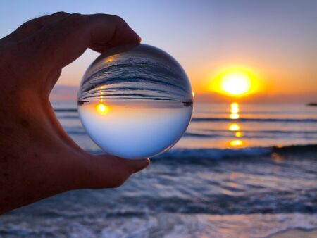 Womans hand holding a crystal ball, looking through to the ocean and sky at sunrise. Creative photography, crystal ball refraction Banco de Imagens