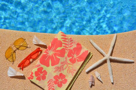 Summer holiday flat lay. Yellow sunglasses, red sunglasses, starfish, and seashells on the poolside. High angle view with copy space,