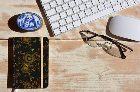 Modern desktop, Wireless computer keyboard and mouse with notebook and pair of glasses. Flat lay photography, with copy space