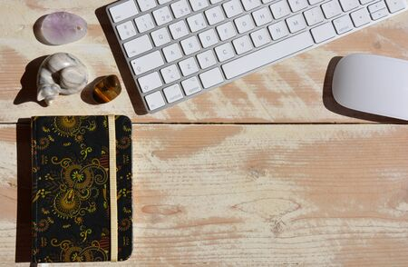 Modern workspace, wireless keyboard and mouse, notebook and semi precious gemstones including tigers eye. Flat lay high angle view with copy space.
