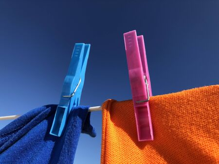Bright and colourful clothes hanging on a washing line, drying in the sun. Plastic clothes pegs.