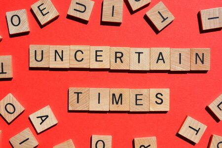 Uncertain Times, words in wooden alphabet letters red background
