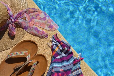 Summer flat lay items, straw hat, beach wrap and sandals on the side of a blue tiled swimming pool with copy space. Stok Fotoğraf