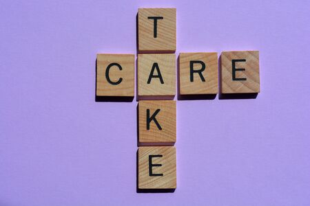 Take Care, crossword in wooden letters on purple background 写真素材
