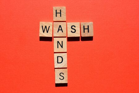 Wash Hands, words in 3d wooden alphabet letters in crossword form isolated on red background