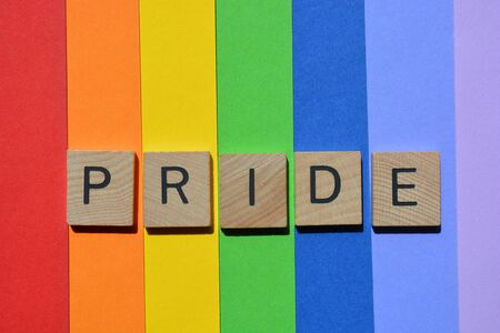 Pride, word in 3d wooden alphabet letters isolated on rainbow striped coloured background Imagens
