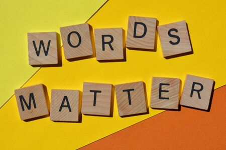 Words Matter, in wooden alphabet letters isolated on bright yellow and orange background