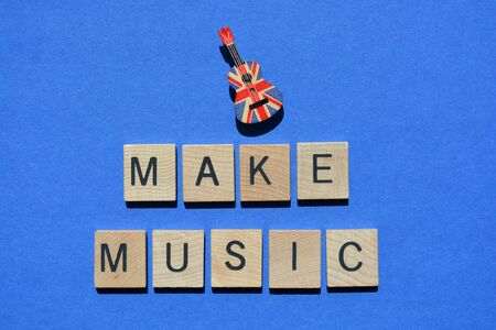 Make Music, words in 3d wooden alphabet letters isolated on blue background, with a ukulele pin decorated with a Union Jack flag pattern