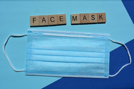 Face mask, word and a disposable 3 ply non-surgical face mask with elastic ear loops isolated on blue background Stock Photo