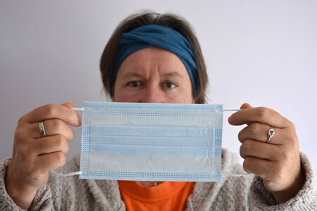 Woman holding a disposable 3ply non-surgical face mask with elastic loops, selective focus on the mask Stock Photo