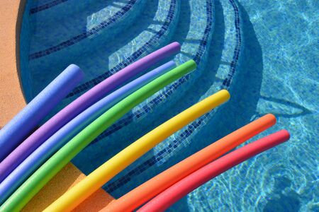 Brightly colored pool noodles on poolside, on a bright, sunny summer day