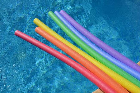 Rainbow coloured pool noodles floating in a swimming pool on a bright and sunny day