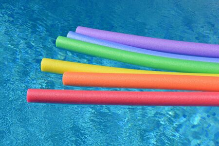 Rainbow coloured pool noodles floating in a swimming pool on a bright and sunny day.