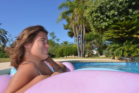 Beautiful young woman floating on a lilo in a swimming pool on a bright and sunny summer day