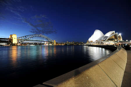 Panoramic view of Sydney Opera House and Harbour Bridge at night, wide angle view