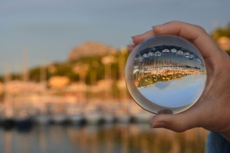 Looking through a crystal ball to the port of Javea and Montgo mountain on the Costa Blanca, Spain. Creative refraction photography. Concept, Dream Holiday,