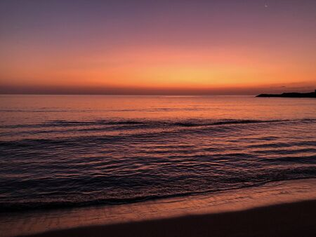 Spectacular seascape at dawn, bright red and orange sky relected in the ocean, with a crescent moon visible in the sky