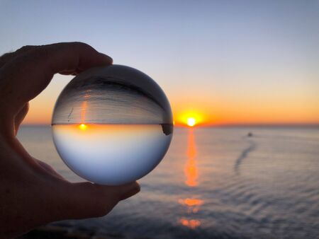 Woman's hand holding a crystal ball, looking through to sea and sky at dawn. Creative Concept, dream travel. Crystal ball refraction photography