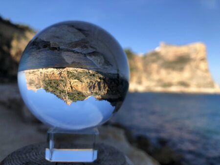 Coastal view, sea and cliff trough a crystal ball, Cala Moraig, Alicante Province, Spain