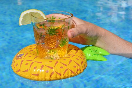 Woman holding glass of water with slice of lemon, in an inflatable pineapple drinks holder in a swimming pool. Close up of hand and plastic cup. Summer vibes, keeping cool in summer