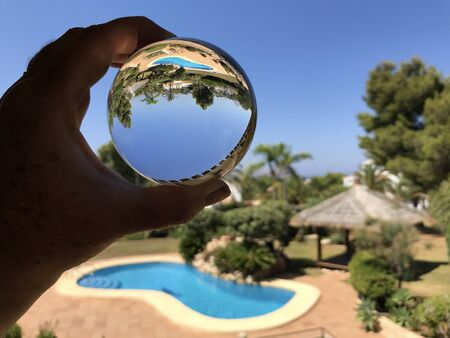 Crystal ball in hand, refraction photography. Looking through lens to a swimming pool and garden in sunshine. Dream holiday.