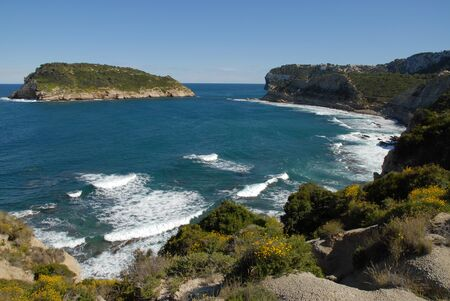 Coastal view with waves breaking on the shoreline in spring,  to the island of Portichol from the headland at Cap Prim, Javea, Alicante Province, Spain