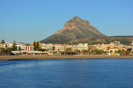 View to the Arenal beach with the iconic Montgo mountain behind on a beautiful, sunny and bright morning in the resort town of Javea on the Costa Blanca, Alicante Province, Spain. Stock Photo