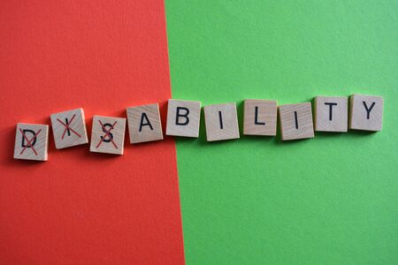 Disability, word in 3d wooden alphabet letters on a multi coloured background with Dis crossed out to leave the word Ability