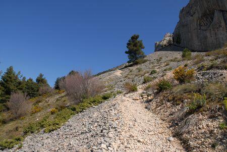 track to Els Frares limestone rock pinnacles across a scree slope, Sierra de Serrella, Comtat, Alicante Province, Comunidad Valenciana, Spain Stock Photo
