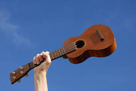 hand holding ukulele against blue sky,  with copy space
