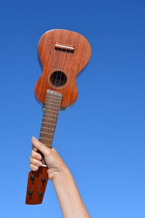 Soprano ukulele  held up against blue sky in a woman's hand, with copy space