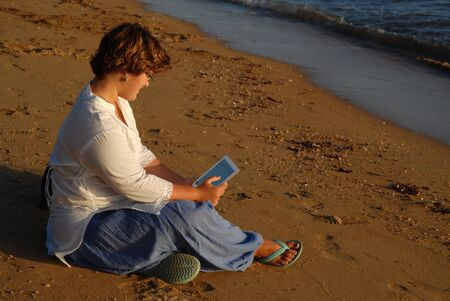 Girl sitting on beach looking at tablet