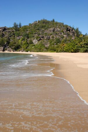 Idyllic coral beach scene with coconut palms and granite boulders,  and waves lapping the shoreline at Radical Bay, Magnetic Island, Queensland, Australia