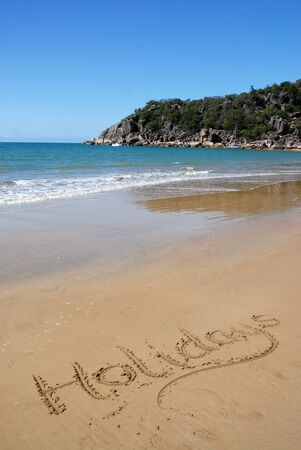 Idyllic beach  view with the word Holidays written on the sand, Radical Bay, Nagnetic Island, Queensland, Australia