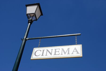 Old fashioned Cinema sign hanging from a lamp post against blue sky in the historic town of Charters Towers, Queensland, Australia