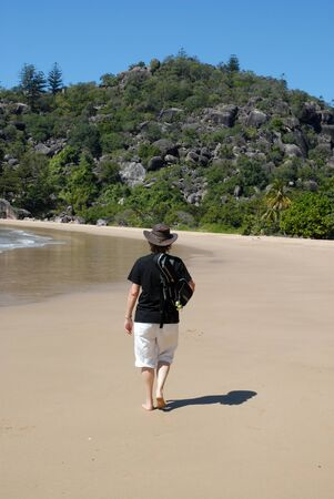 Back view of woman walking  away with a ukulele on her shoulder, on the beach at Radical Bay on Magentic Island, Queensland, Australia Stock Photo