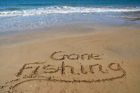 Gone fishing written in sand on the beach with surf and blue sea beyond.