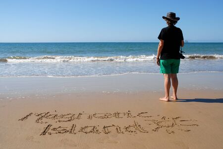 Woman standing on beach holding a camera looking out to sea, with the words Magnetic Island aritten in the wet sand. Queensland, Australia