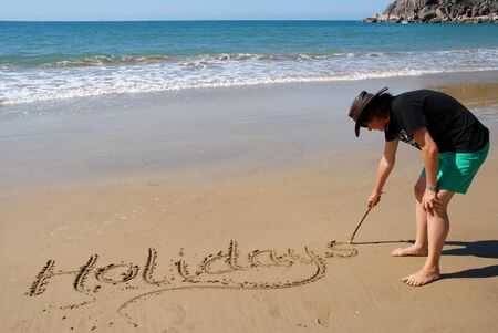 Woman writing the word Holidays in the sand on the beach at Radical Bay, Magnetic Island, Queensland, Australia