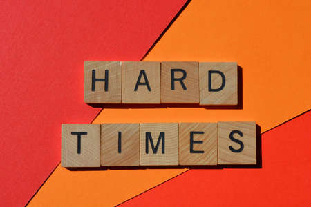 Hard Times, words in wooden alphabet letters on bright red and orange background 版權商用圖片
