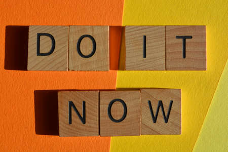 Do It Now, words  in wooden alphabet letters isolated on yellow and orange background