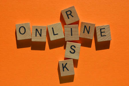 Online, Risk, words in wooden alphabet letters in crossword form isolated on orange background