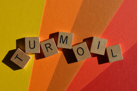 Turmoil, word in wooden alphabet letters on colourful background