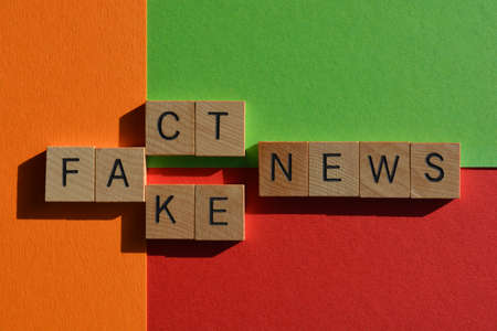 Fact, Fake, News, words in wooden alphabet letters on red, orange nd green background.